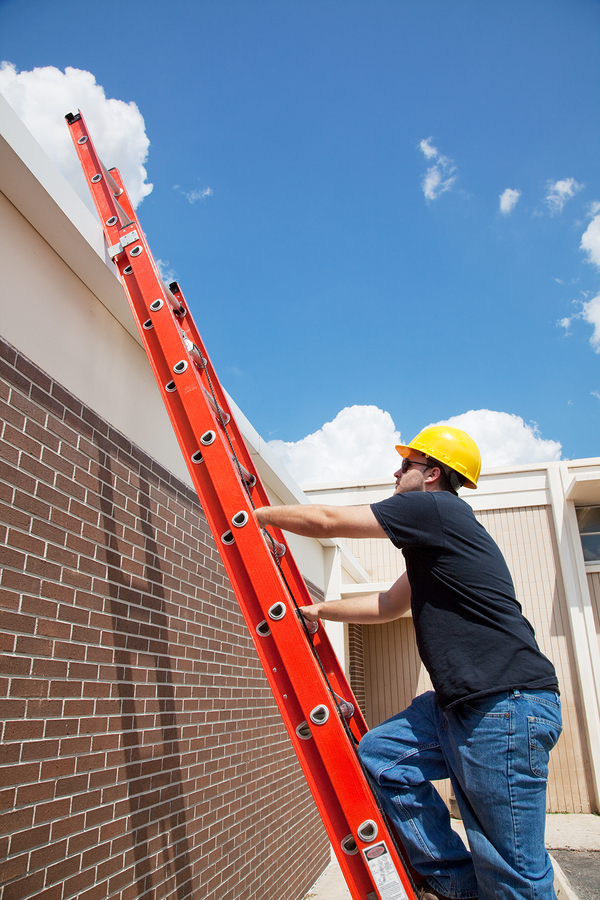 Construction worker climbing up a ladder to the roof of a building.