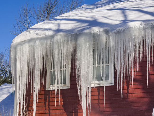 bigstock-ice-dams-and-snow-on-roof-and-82911134