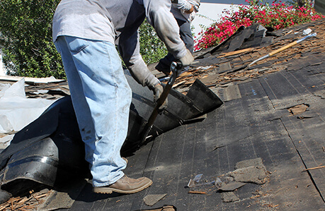 tearing off shingles so new ones can be installed