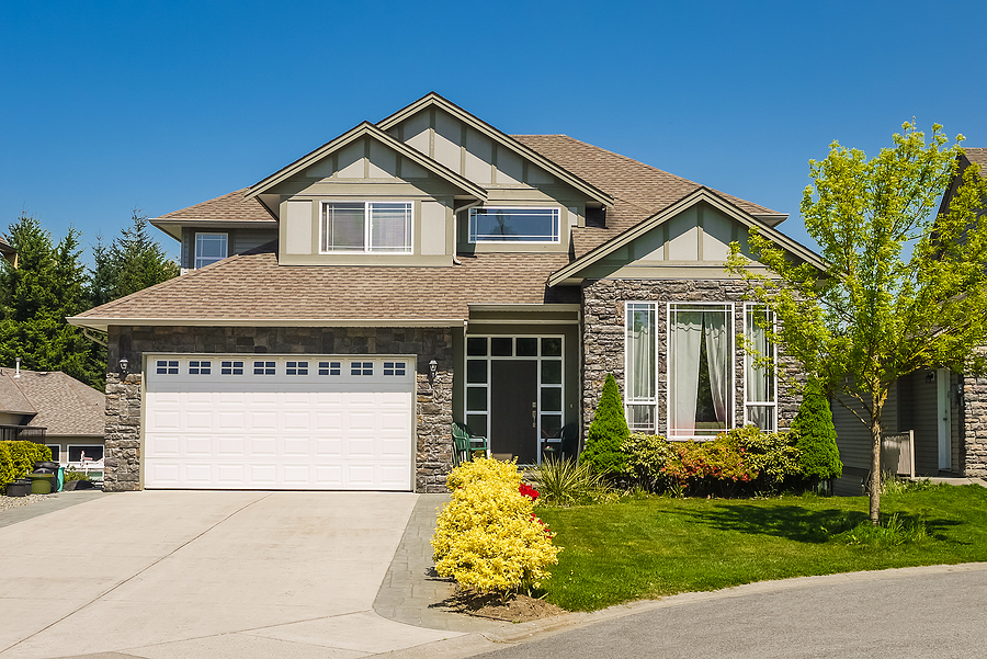 Big family house with concrete driveway to large garage. Residential house entrance with landscaped front yard and a new roof.
