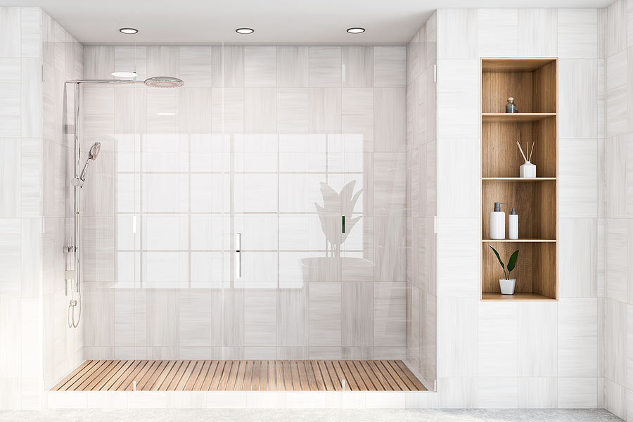Corner of modern bathroom with white wooden walls, concrete floor, comfortable shower stall with glass doors and shelves with cosmetic products.