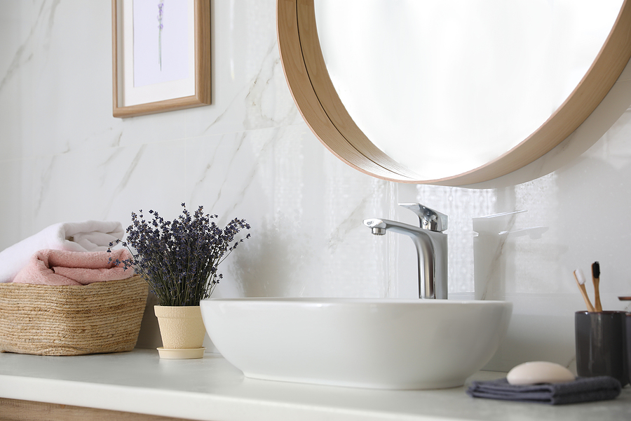 Bathroom counter with vessel sink, flowers and towels in bathroom interior. Idea for design.