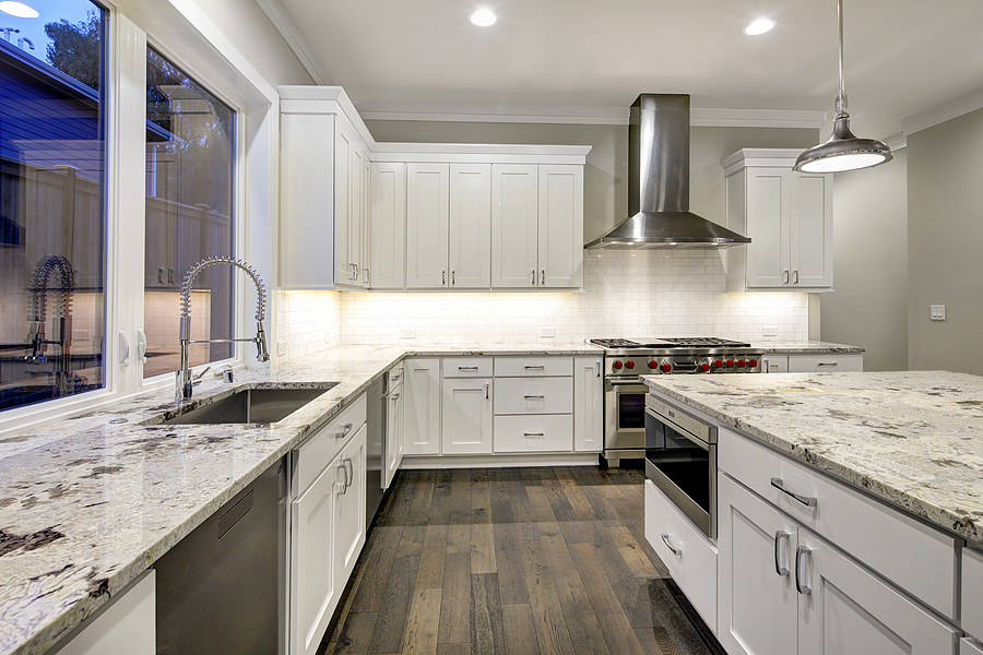 Large spacious kitchen design with white kitchen cabinets white kitchen island with lots of storage white Granite countertops subway tiles and stainless steel appliances.