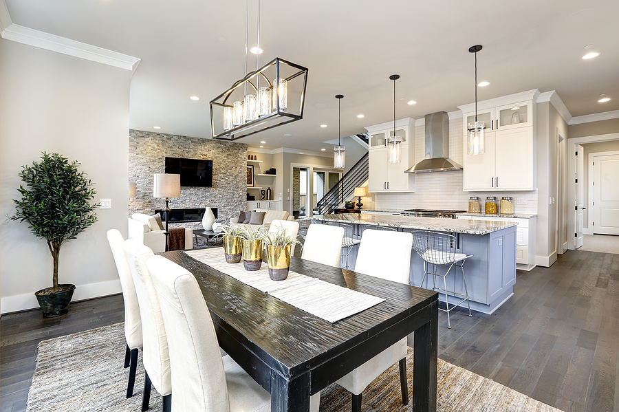 Beautiful modern kitchen in luxury home interior with large island and stainless steel appliances.