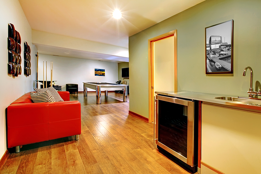 Fun play room home interior. Basement room without windows with pool table TV games.