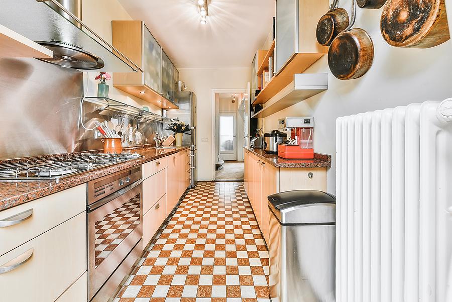 Modern galley kitchen with wooden cabinets and minimalist design.